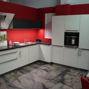 Bauformat L-Küche in weiß mit Edelstahl Griffleisten und schwarzer Arbeitsplatte
