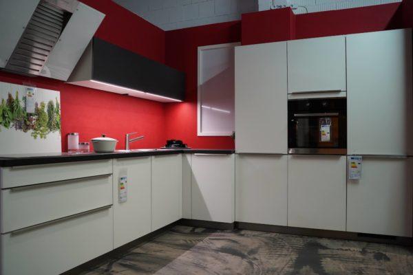 Bauformat L-Küche mit weißen Fronten Edelstahl Griffmulden und schwarem Oberschrank