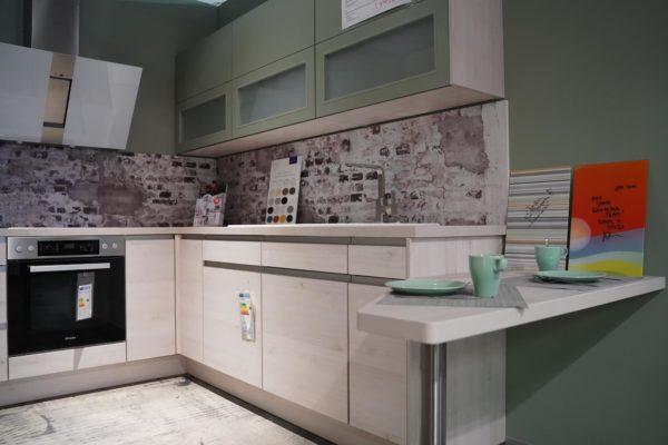 Nobilia Riva Designküche U-Form Edelstahl Griffmulden mit grünem Oberschrank und Tresen